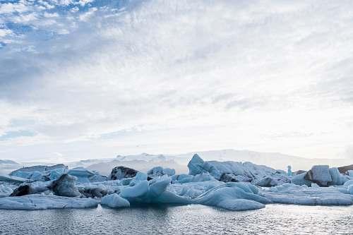 glacier rock formation beside body of water ice