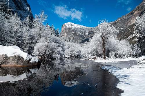 snow snow capped mountain near river at daytime blue