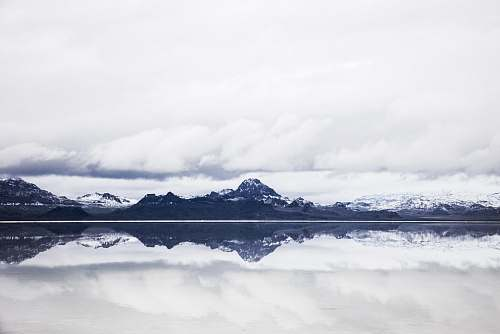 nature snow capped mountain under white clouds in mirror reflection photography mountains