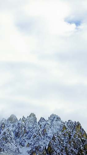 nature snow covered mountain under white clouds during daytime outdoors
