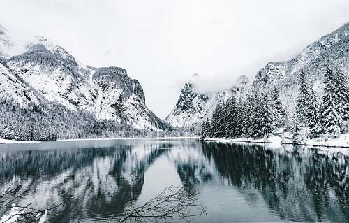 ice snow-covered mountains and trees near lake outdoors