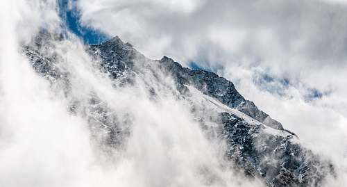 nature snowy mountain covered with fogs clouds