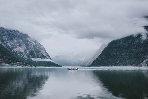 snow white and gray boat in the middle of calm body of water near mountain under white sky nature