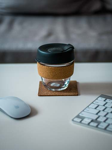 keyboard covered jar between Magic Mouse and Keyboard on desk glass