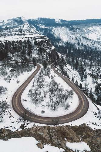 mountain aerial photography of curved road in between snow covered ground overlooking mountain and trees under white sky at daytime trees
