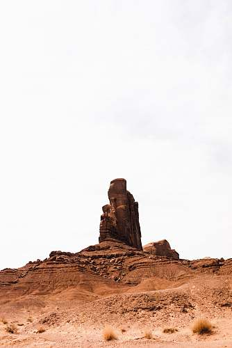 outdoors brown rock formation under white sky monument valley
