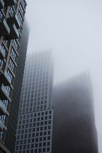 grey city with high-rise buildings during foggy season city