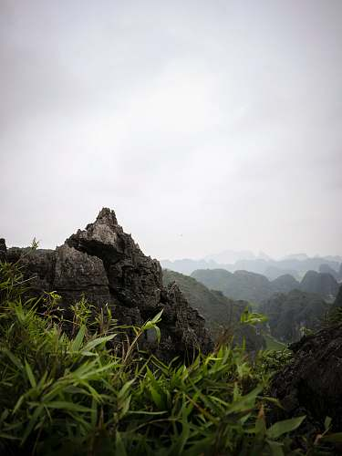 outdoors grass near rock under cloudy sky at daytime slope