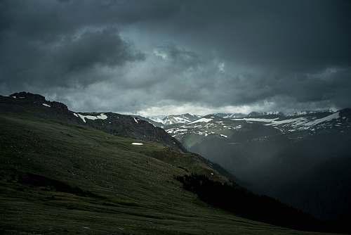 outdoors green mountain under cloudy sky mountain