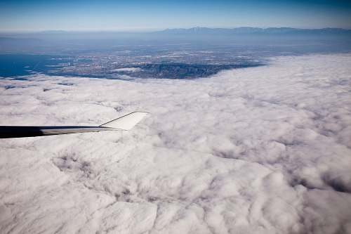 outdoors grey aircraft wingtip on flight above white clouds scenery