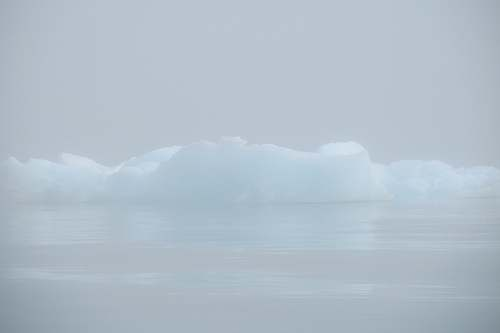 ice icebergs on body of water blue