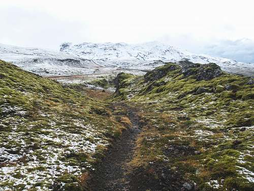 mountain pathway between green grass hill towards snow capped mountain outdoors