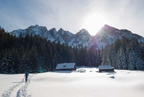 winter person walking on snowfield near mountain range mountain range