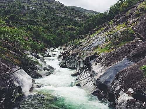 waterfall river between mountain peaks water