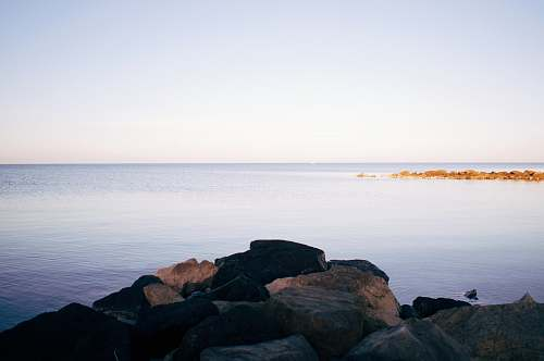 shoreline rocks beside body of water water
