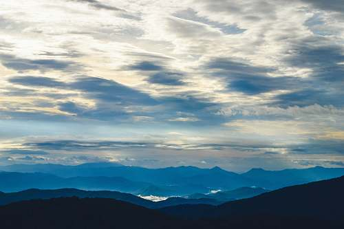 cloud silhouette of mountains under sea clouds sky