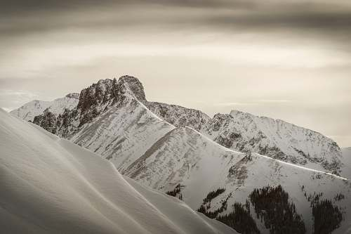 mountain snow-covered mountains under gray clouds during daytime alps