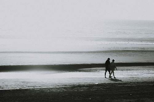 outdoors two person walking on seashore ocean