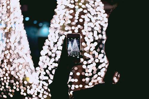dark person taking picture of Christmas trees lights