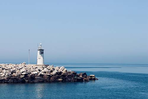 sea photograph of white lighthouse on rocks water
