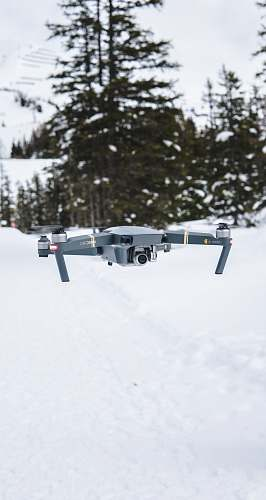 flight gray flying quadcopter near trees with snow winter