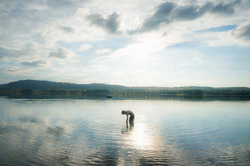 water person standing on body of water lake