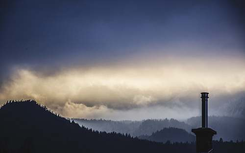 cloudy lighthouse on mountain trees