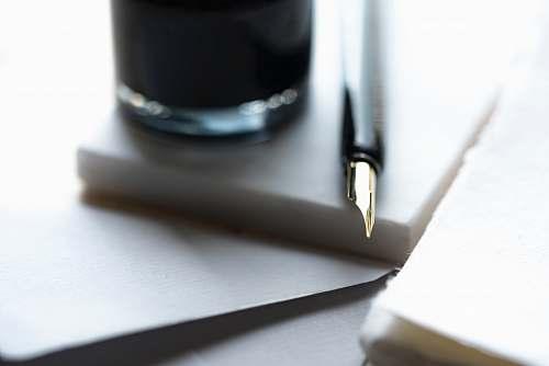 nib fountain pen beside the glass calligraphy