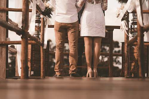 wedding couple standing on front of brown table at daytime human