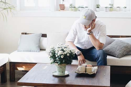 plant man sitting on white fabric sofa infront of coffee table inside the living room couch