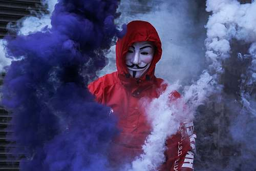 human man wearing red jacket surrounded by purple and white smoke person