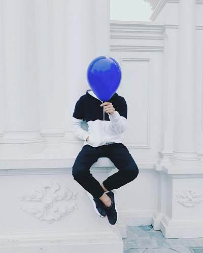 person person sitting on white concrete pavement holding blue balloon at daytime human