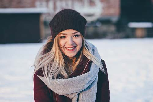 woman smiling woman wearing brown scarf and maroon coat on snow field girl