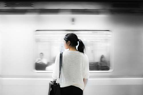woman woman in white elbow-sleeved shirt standing near white train in subway human