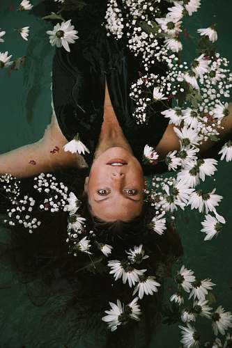 person woman swimming covered by white daisies woman