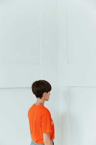 human woman wearing orange shirt facing white wall person