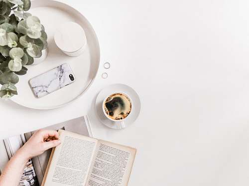 page flat-lay photography of person holding opened book on tabletop beside cup of black coffee text