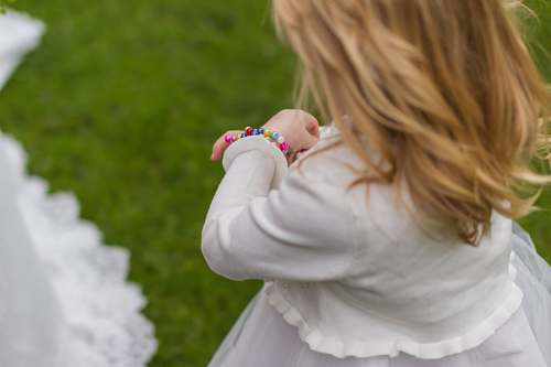 human girl wearing white dress holding her bracelet people