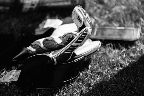 human greyscale photo pair of gloves on grass field black-and-white