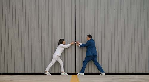 human man and woman standing beside gray wall people
