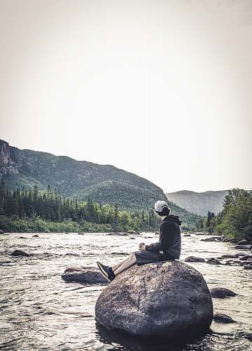 human man sitting on rock viewing river and mountain during daytime wilderness