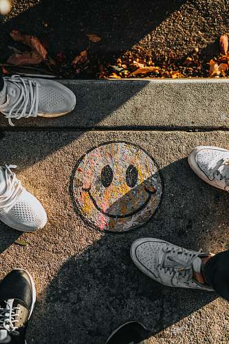 human smiley paint on gray ground in front of people people