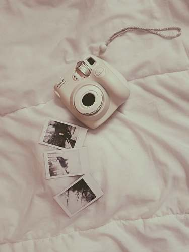 human white Fujifilm instant camera on white comforter people