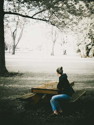 human woman in black hoodie and blue denim jeans sitting on picnic bench sitting
