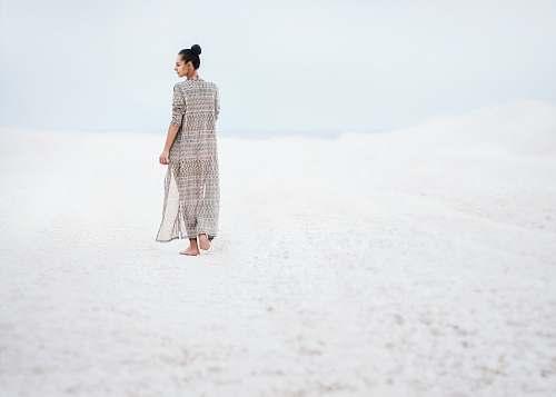 people woman in gray dress walking on sand human