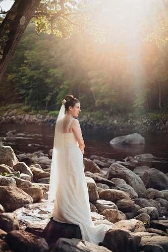 nature woman standing on gray rock near lake during sunset rock