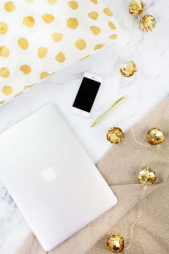 electronics gold iPhone beside pen on white textile mobile phone