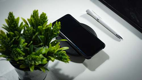 cell phone smartphone place on wireless charger on table electronics