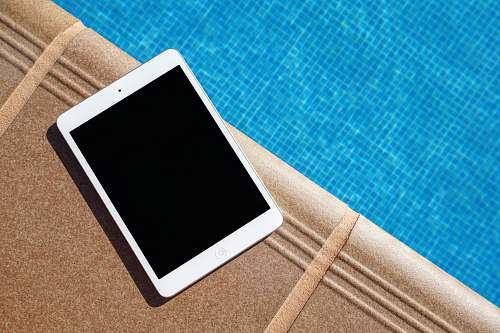 tablet white iPad beside swimming pool tech