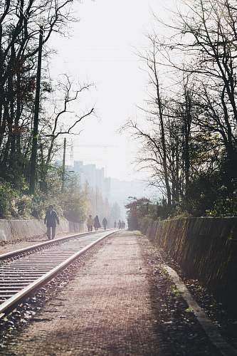railway group of people walking on railroad train track